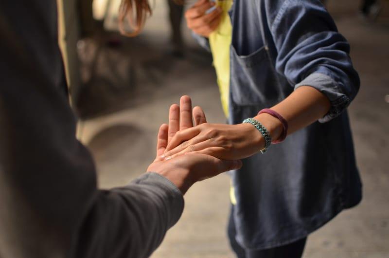 Das Bild zeigt wie eine Person einer anderen die Hand reicht.
