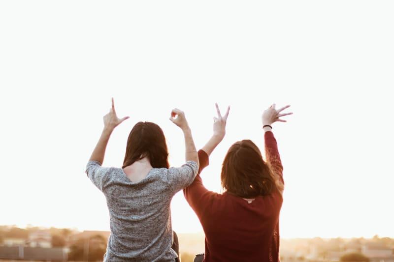 """Zwei Menschen symbolisieren mit ihren Händen """"Love"""""""