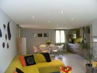 Küche mit weißer Spanndecke und Lichtern mit grünem Sofa