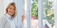 Blonde Frau öffnet Fenster Insektenschutzsysteme Sturma
