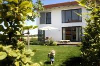 Weißes Haus mit großen grauen Fenstern Garten Kind