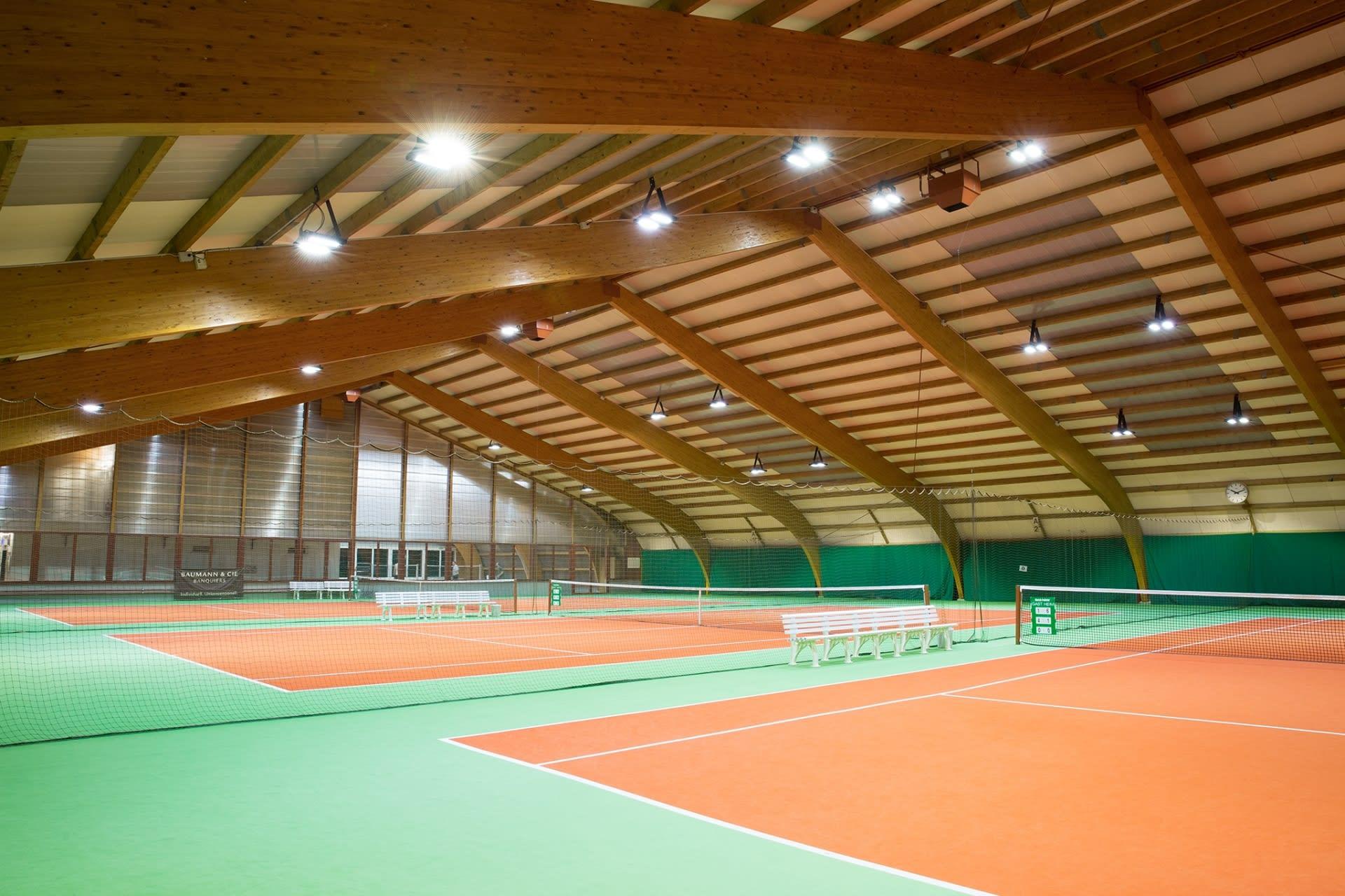 Tennishalle mit Beleuchtung und Grün, rotem Boden