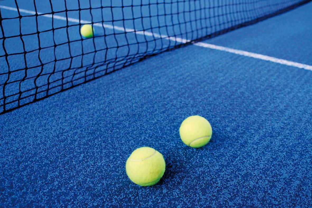 Tennisboden blau mit drei Tennisbällen und Netz