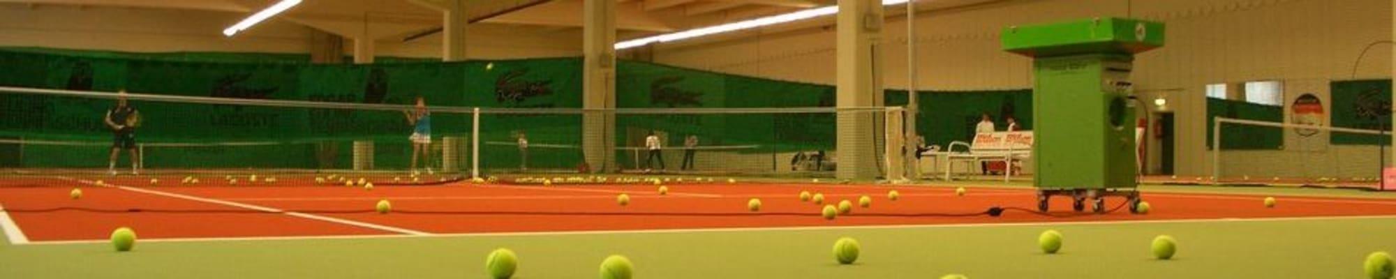 Indoor Tennishalle mit Tennisspieler, Tenniswurfmaschine und vielen Tennisbällen