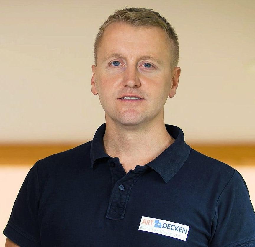 Herr Binder Profilbild mit Poloshirt und Logo darauf