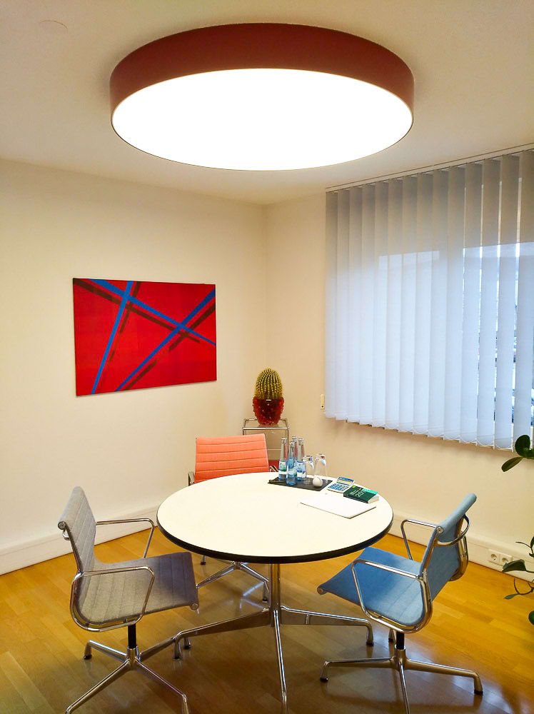 Arbeitszimmer mit großer runder warmweißer Leuchte an der Decke