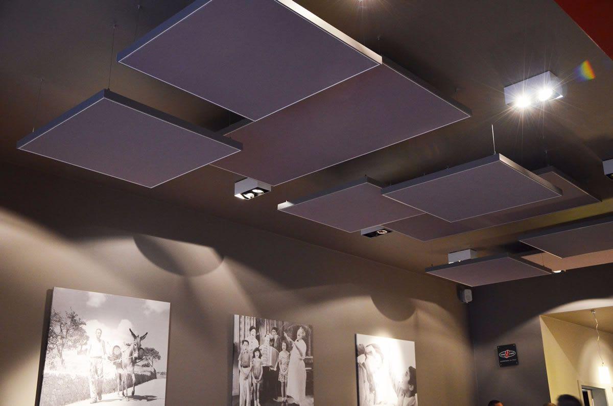 Großer Raum mit Bildern und Akustikdecken dunkel grau