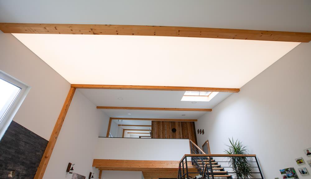 Wohnraum mit Flur und Treppe mit weißer Spanndecke leuchtend