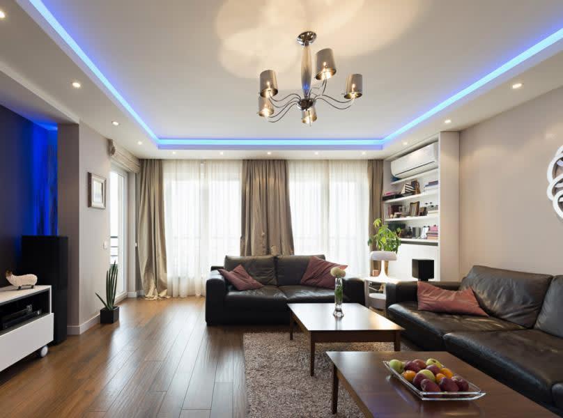 Wohnraum mit Lackspanndecke, Kronleuchter, LED Panels und punktuellen Leuchten