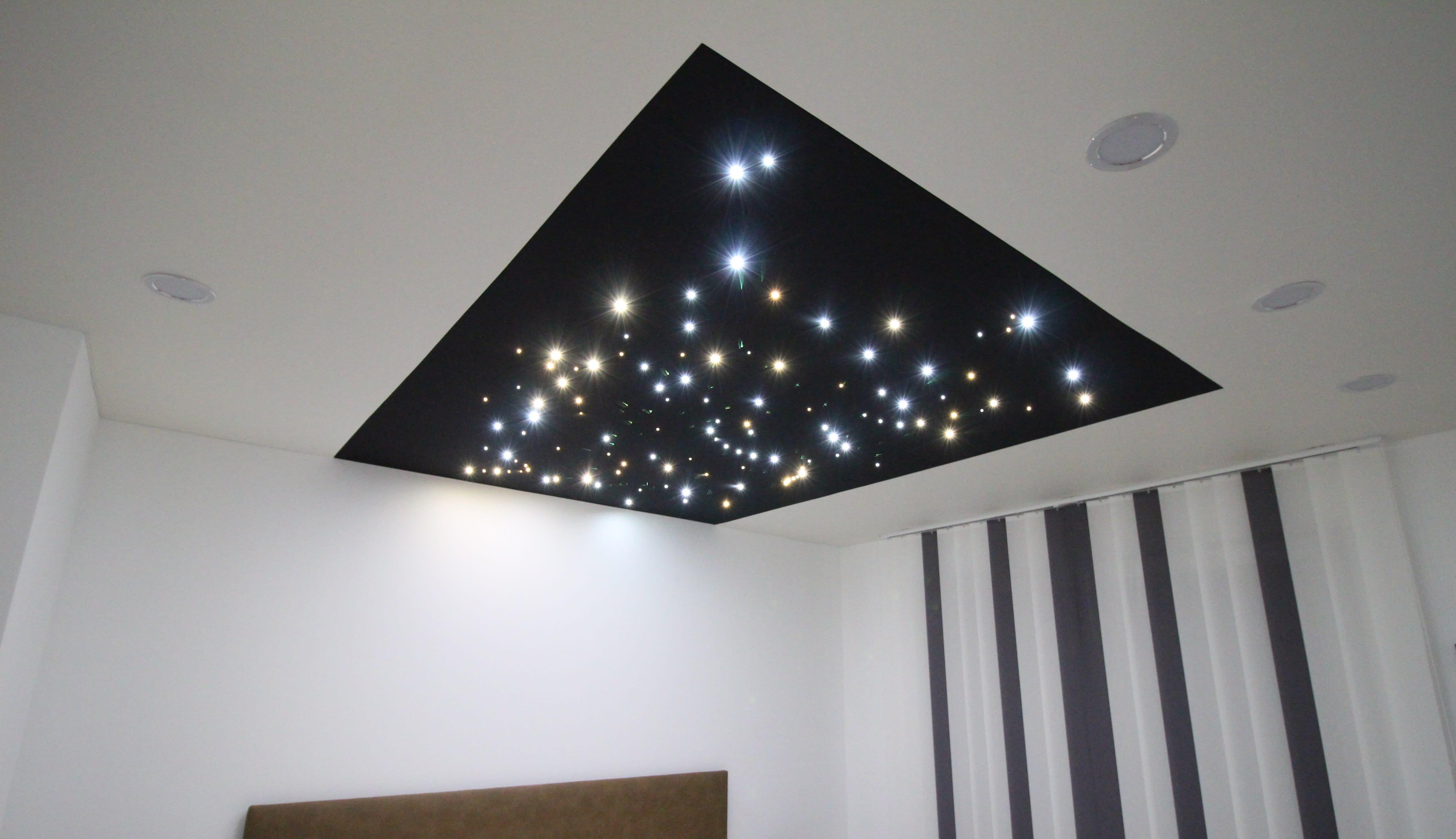 Wohnraum mit weißer Spanndecke und integrierten Sternenhimmel