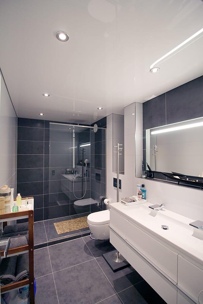 Badezimmer mit weißer Lackspanndecke und punktuellen Leuchten