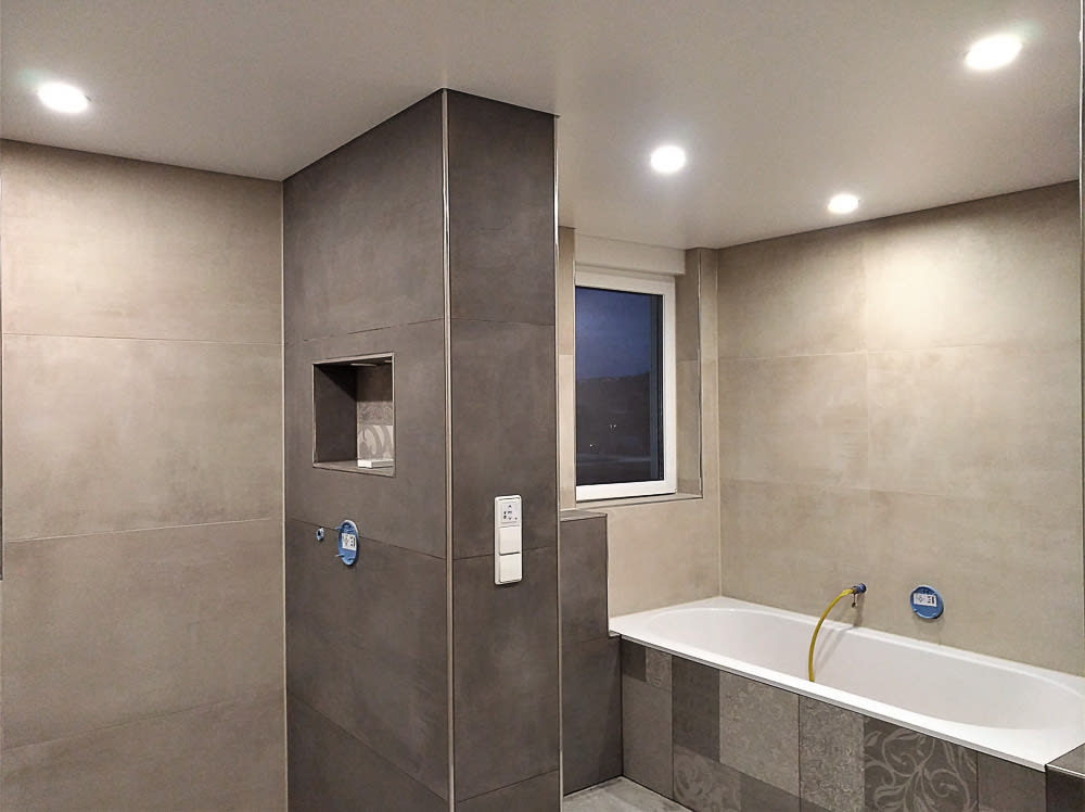Badezimmer weiße Spanndecke mit integrierten Leuchten und Steinwänden
