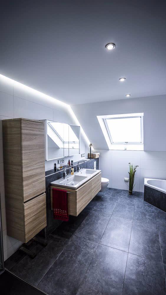 Badezimmer mit weißer Decke und integrierten LED Panels und runden leuchten