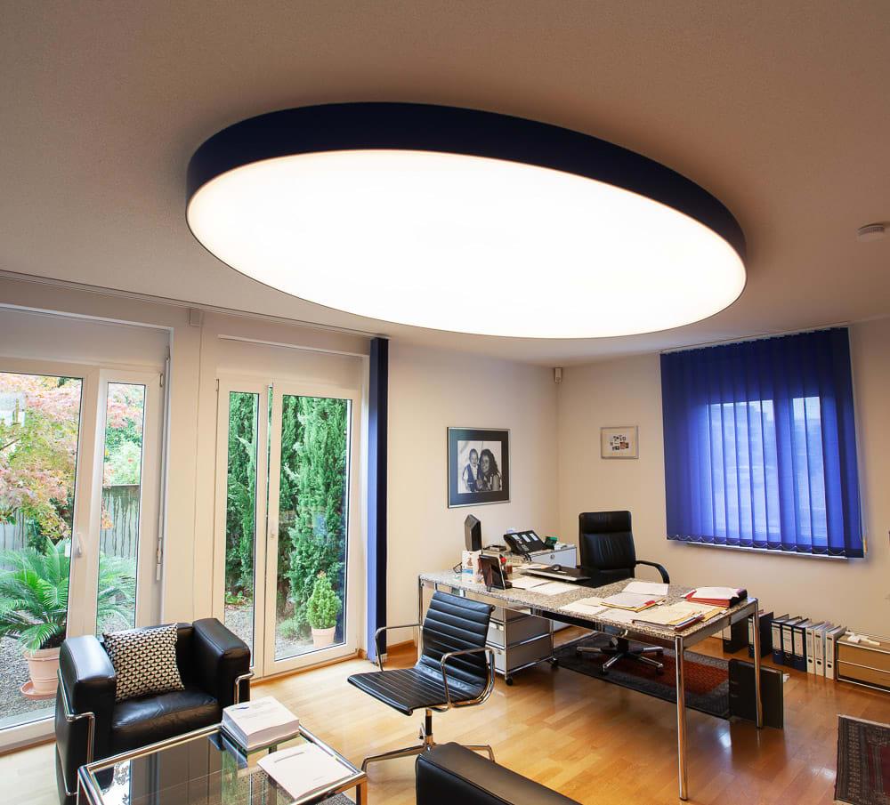 Geweberaum mit großer ovaler Leuchtdecke über Schreibtisch