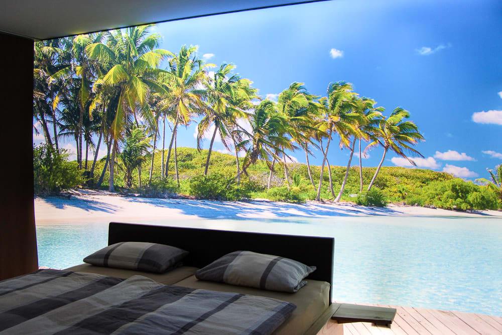 Schlafzimmer nach Sanierung mit leuchtender Motivwand mit Palmen und Strand Motiv