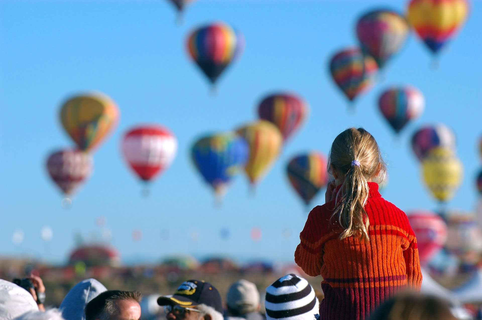 Leute vor fliegenden Heißluftballons