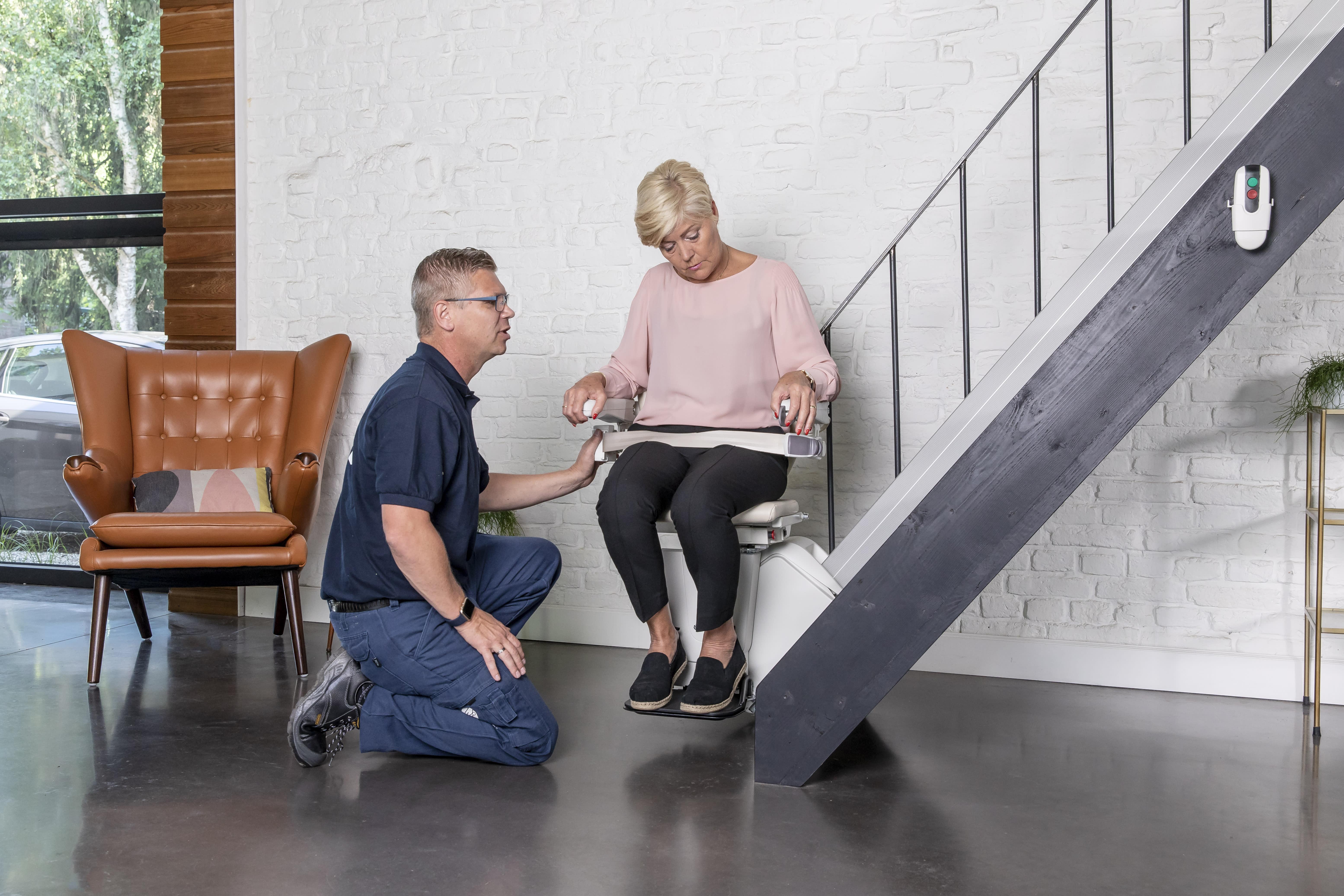 Frau sitzt in Treppenlift und wird beraten