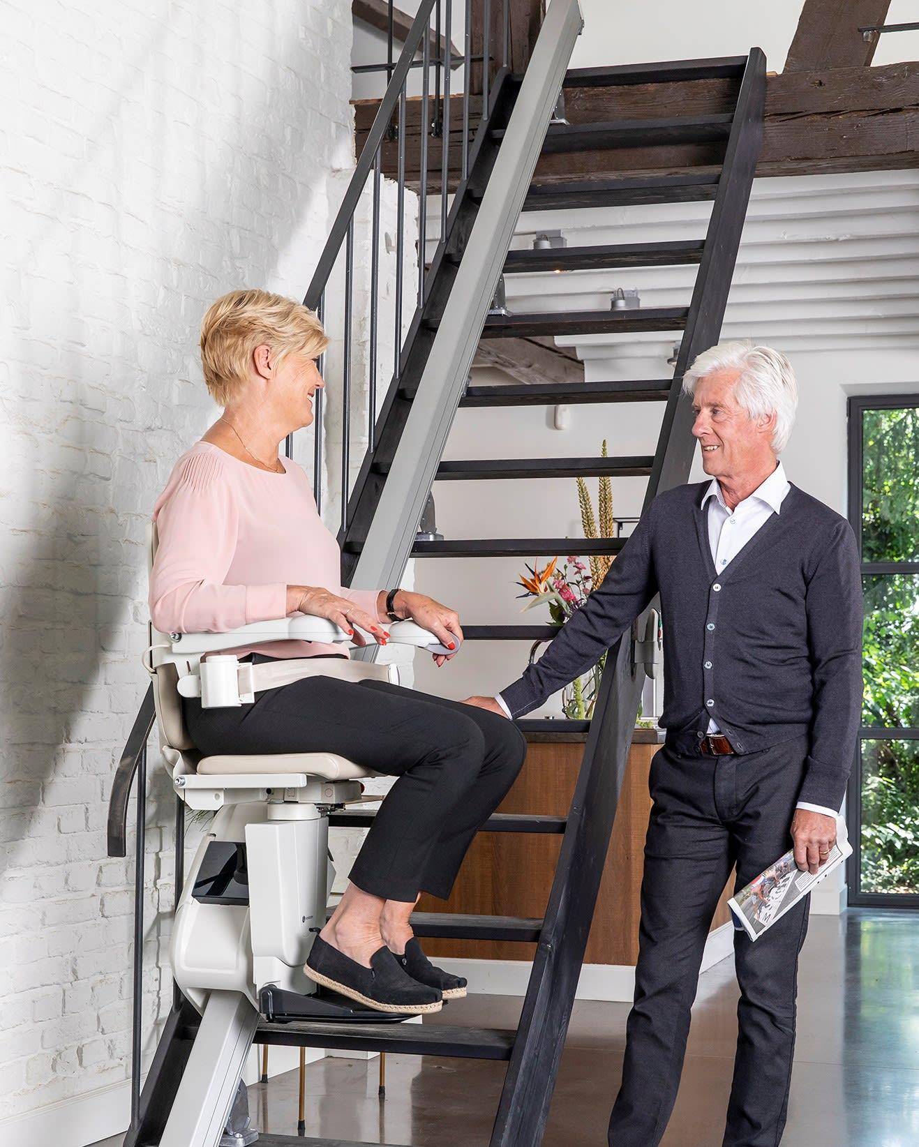 Frau nutzt einen Treppenlift