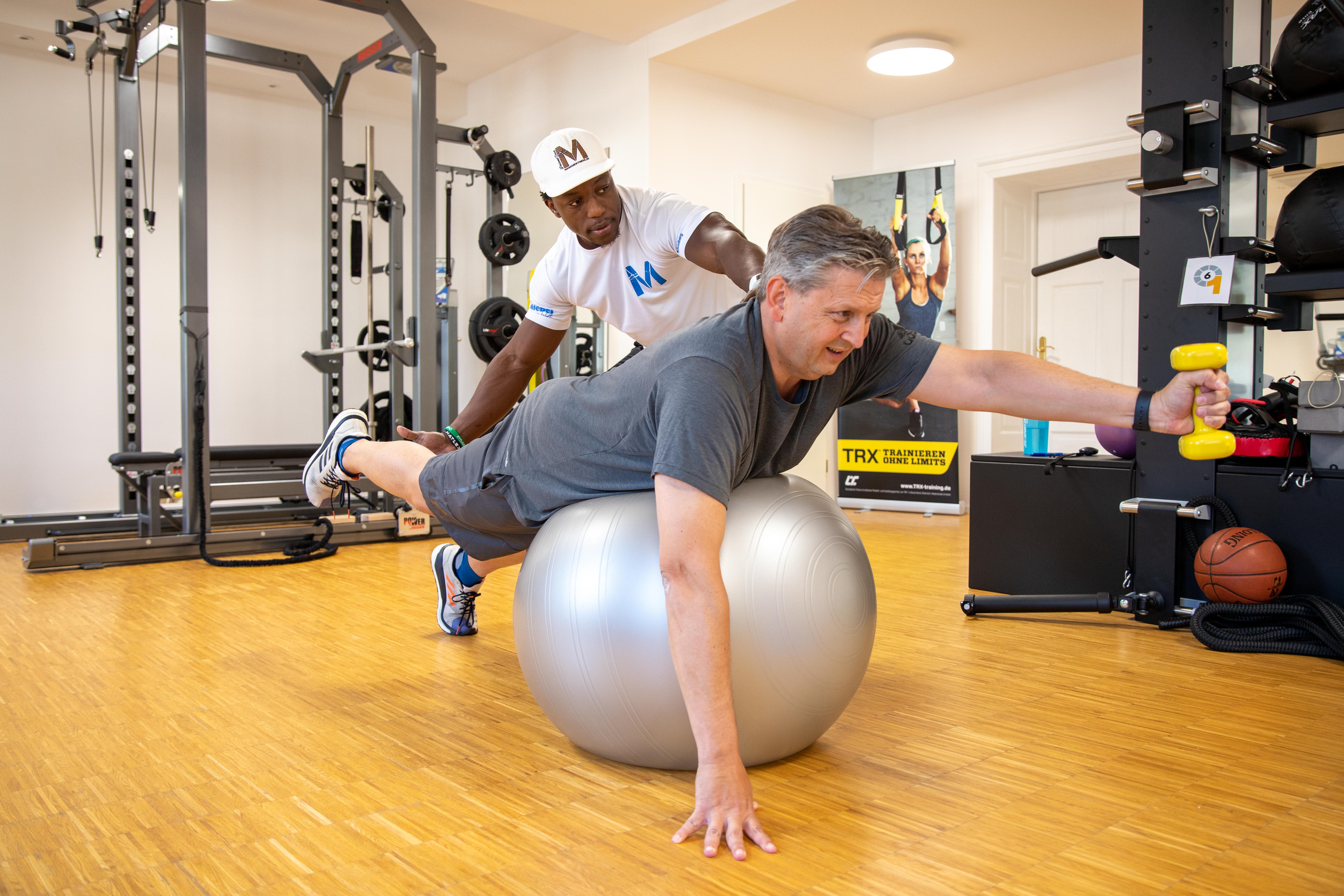 Personal Trainer mit Kunde Ballübung liegend