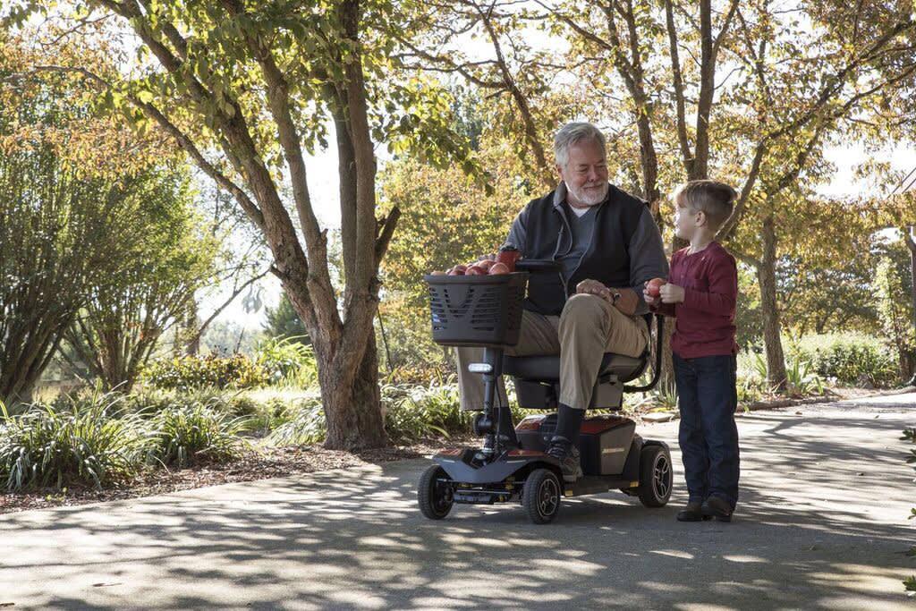 Mann auf Elektromobil mit Enkel