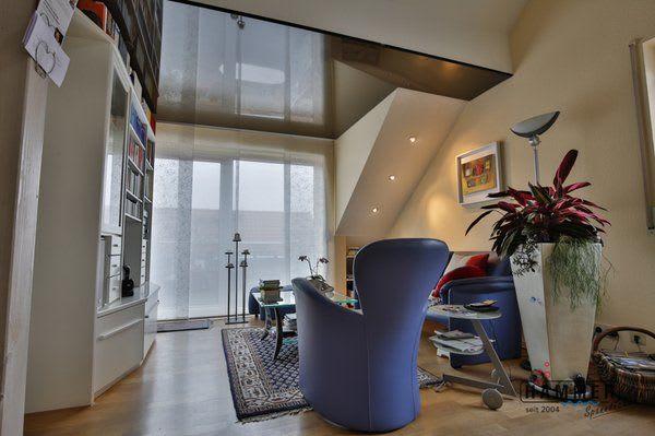 Spanndecke schwarz Wohnzimmer mit blauem Sessel