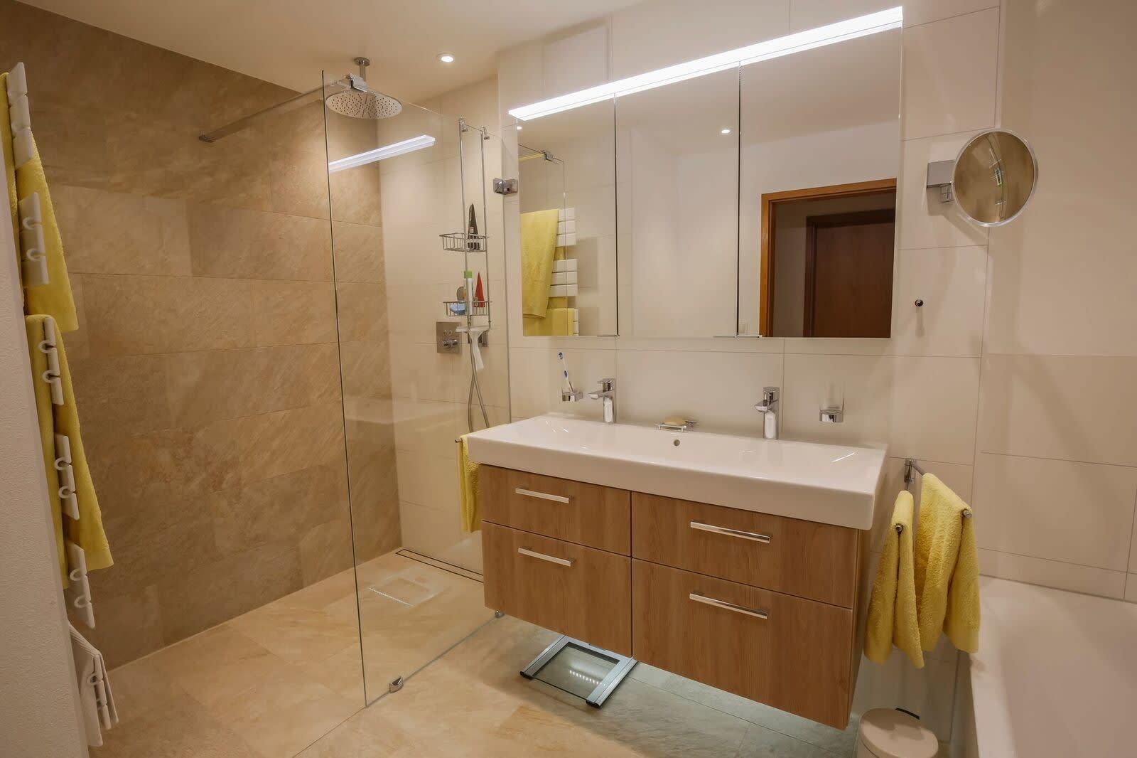 Badezimmer mit heller Spanndecke und Beleuchtung offener Dusche und Holzausstattung