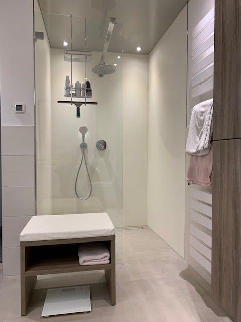 Badezimmer mit offener Dusche und Holzschrank