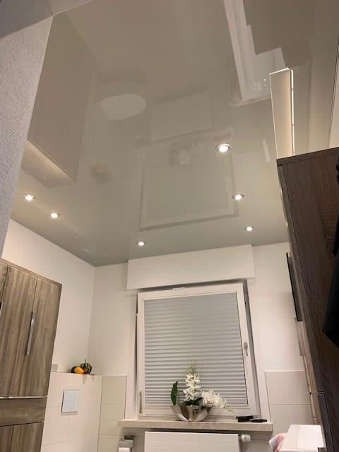 Badezimmer mit weißer Spanndecke und Beleuchtung