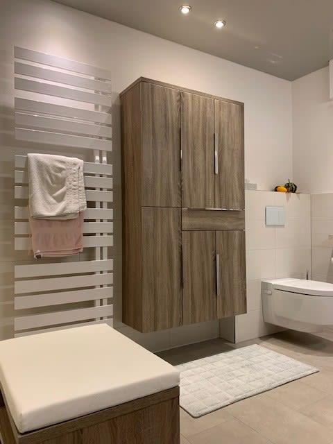 Badezimmer mit Handtuchheizung und Holzschrank