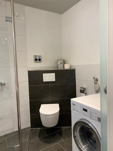 Badezimmer mit schwarzen Fließen und heller Spanndecke