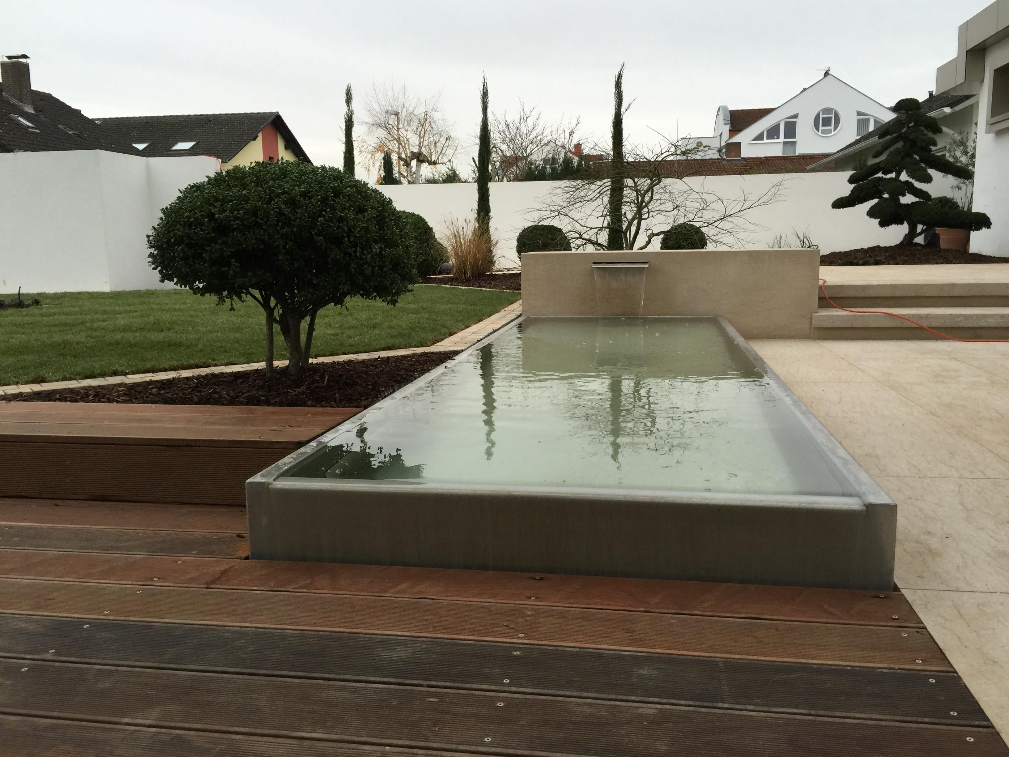 Springbrunnen aus hellem Beton mit Beton- und Holzboden