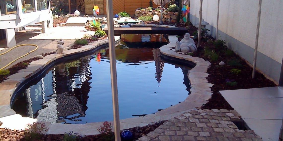 Gartenanlage mit Teich und Buddha Figur