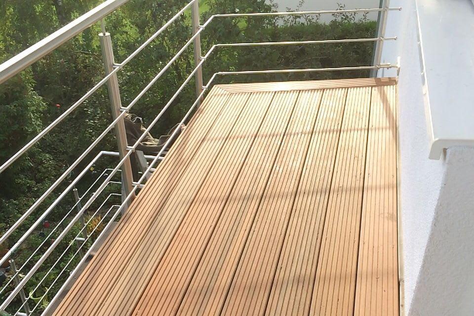 Ecke einer Holzterrasse mit Metallgeländer