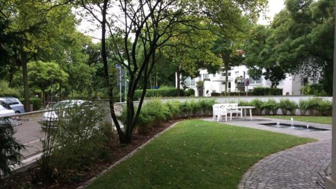 Öffentlicher Park Gartenumgestaltung Nachher mit weißer Bank
