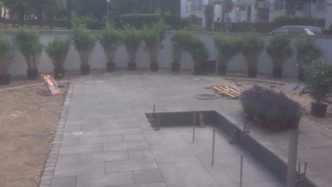 Öffentlicher Park mit weißer Bank und Wasserspiel im Bau