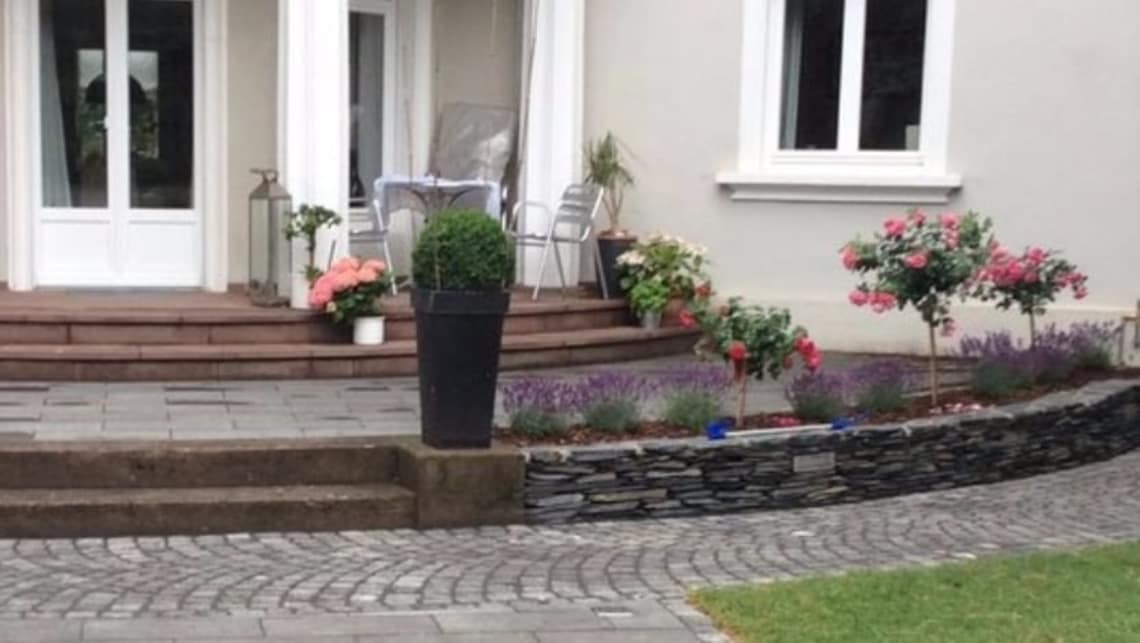 Gartenumgestaltung Terrasse mit Naturstein Mauer und Bepflanzung
