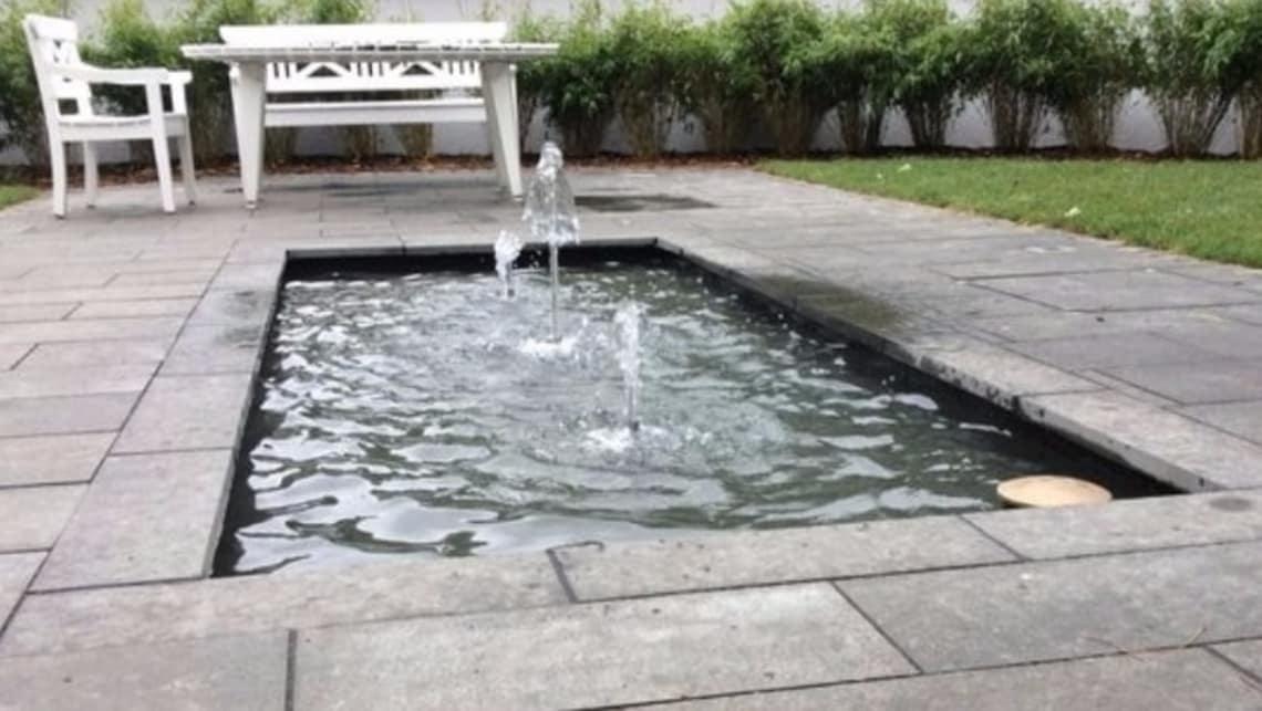 Gartenumgestaltung Wasserspiel und weiße Bank