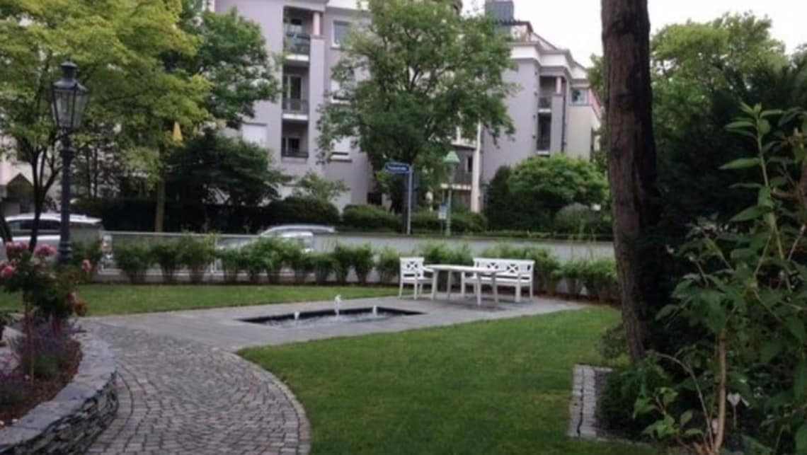 Gartenumgestaltung Sicht auf weiße Bank und Wasserspiel