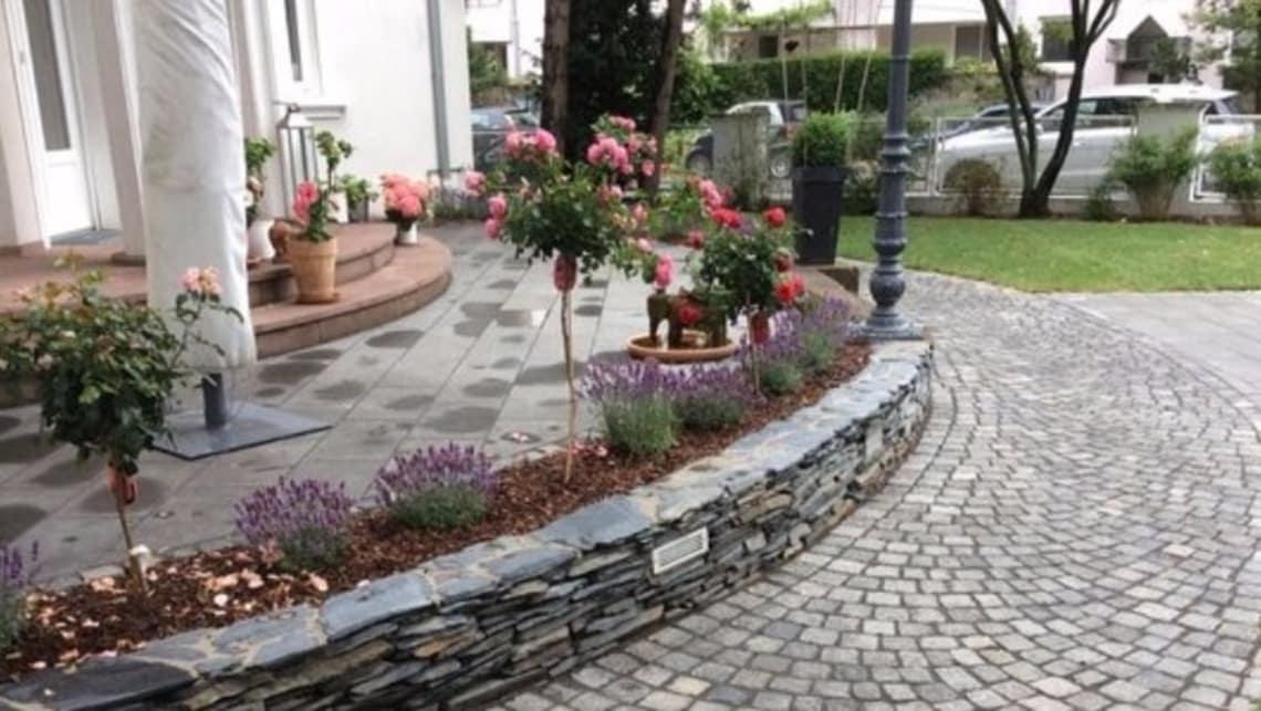 Gartenumgestaltung Sicht auf Terrasse mit Bepflanzung und Naturstein Mauer