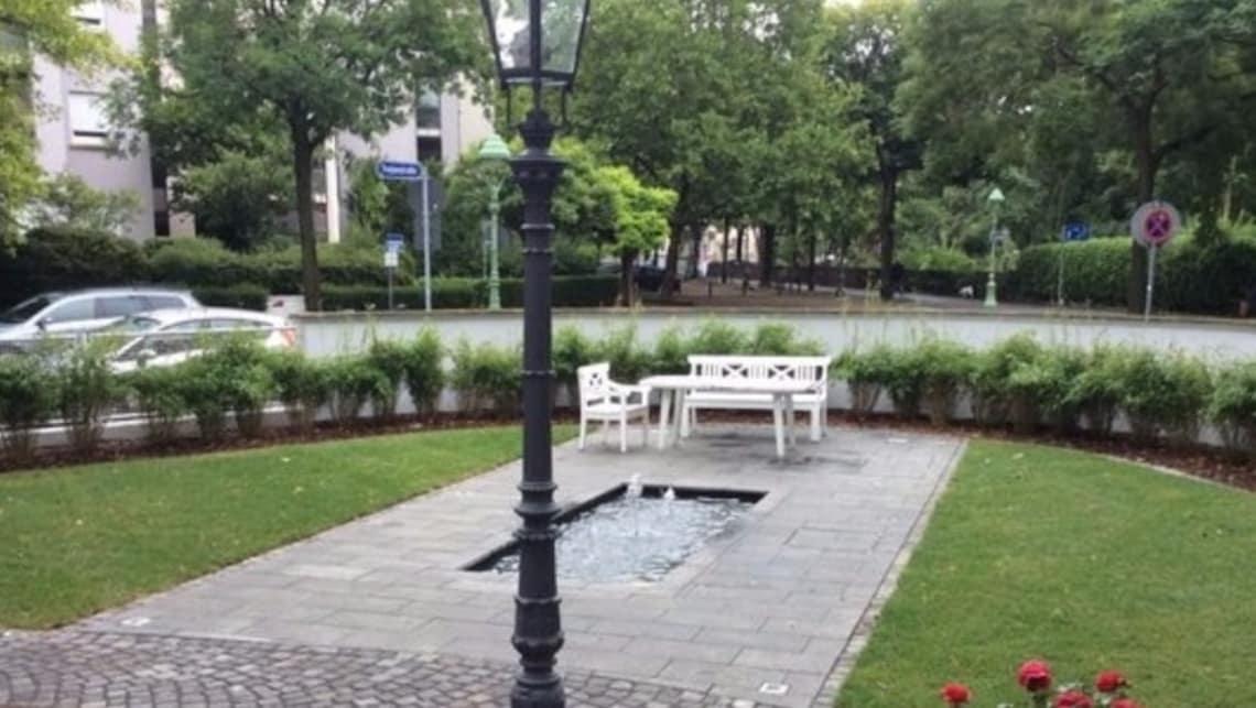 Garten mit weißer Bank, Wasserspiel und Laterne