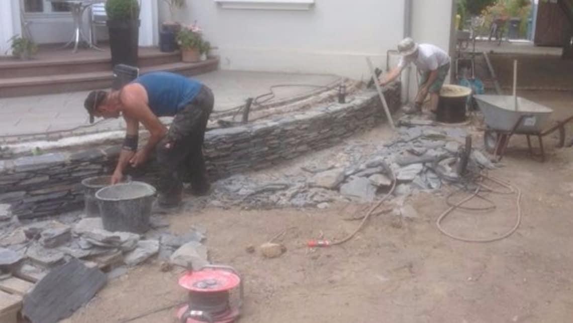 Naturstein Mauer im Bau mit Mitarbeitern