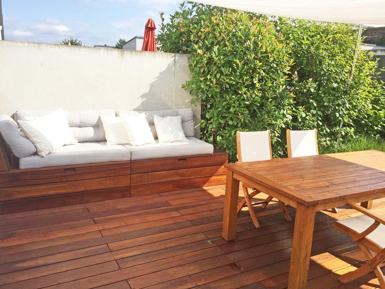 Terrasse mit Holzboden und Tisch mit Stühlen und Sitzecke