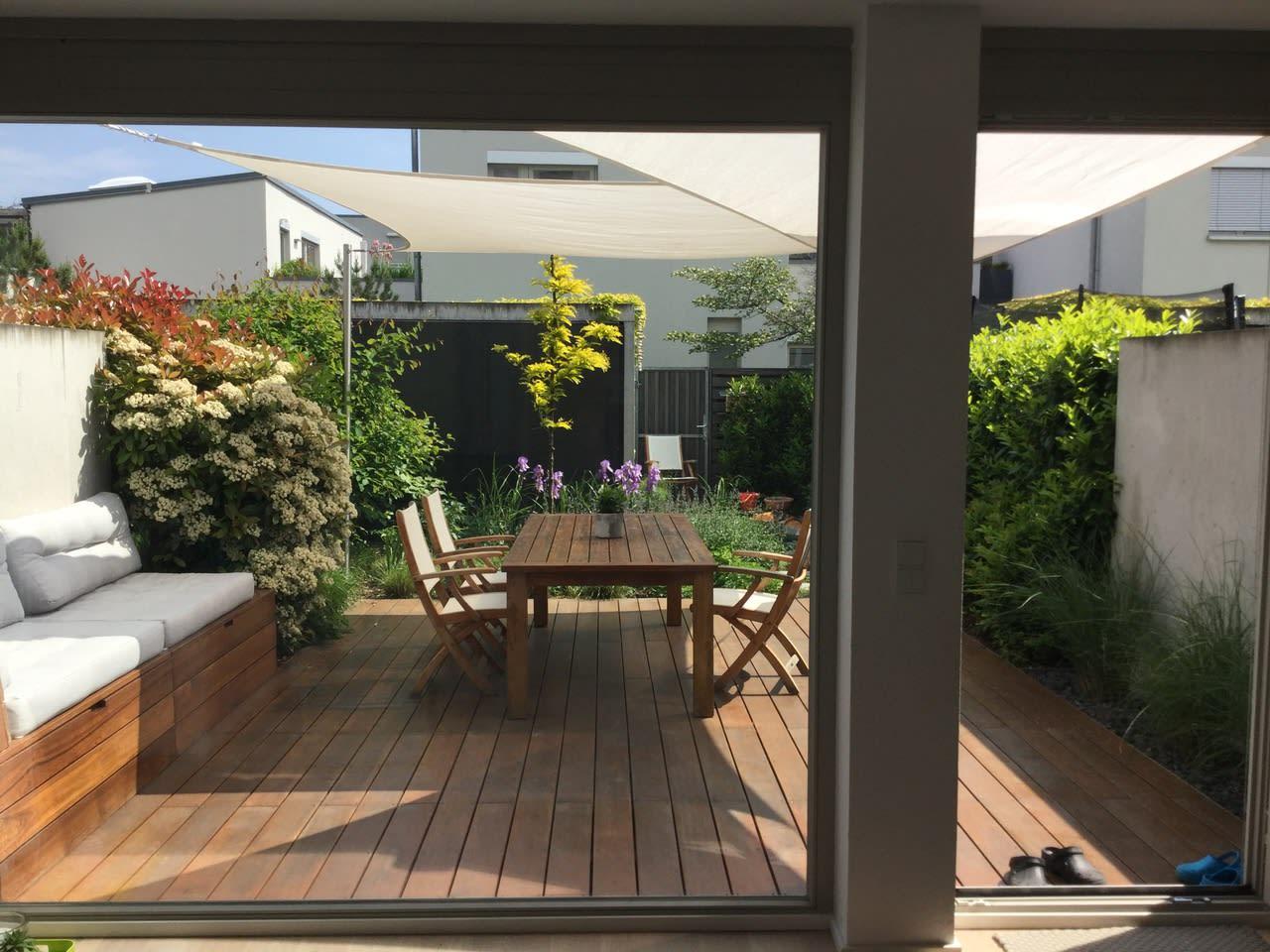 Terrasse mit Holzboden und Tisch mit Stühlen mit Sitzecke Sicht von Innen