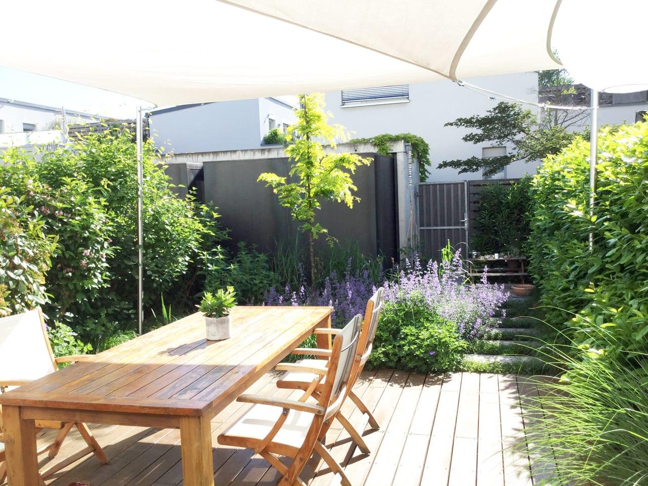 Terrasse mit Tisch und Stühlen und Bepflanzung
