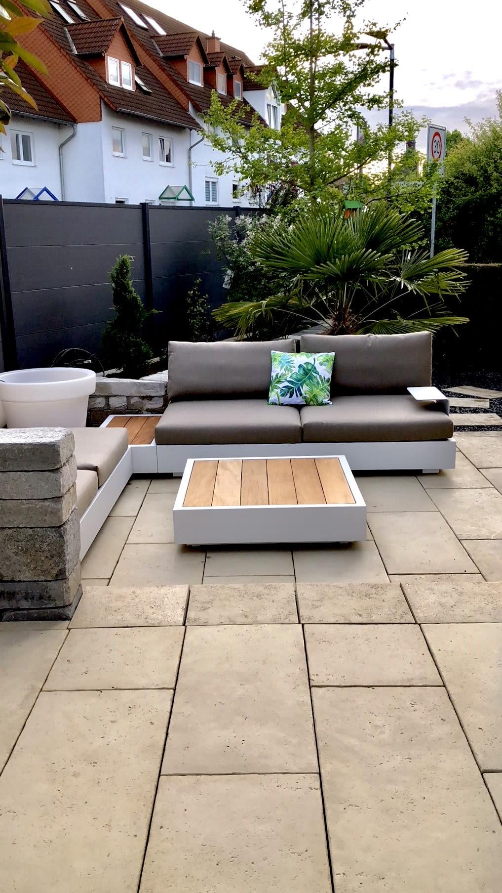 Garten mit Steinplatten und Holzsitzecke