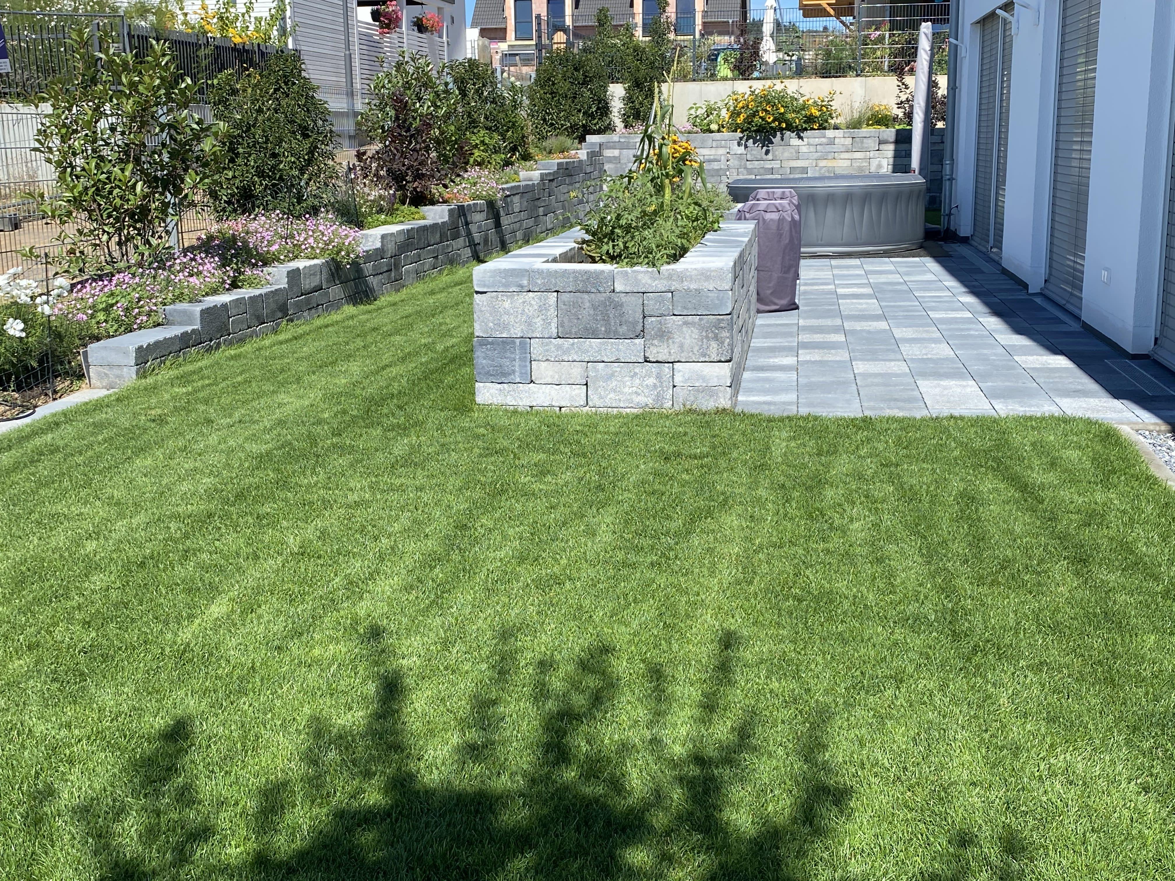 Garten mit grauer Steinmauer und Rasen