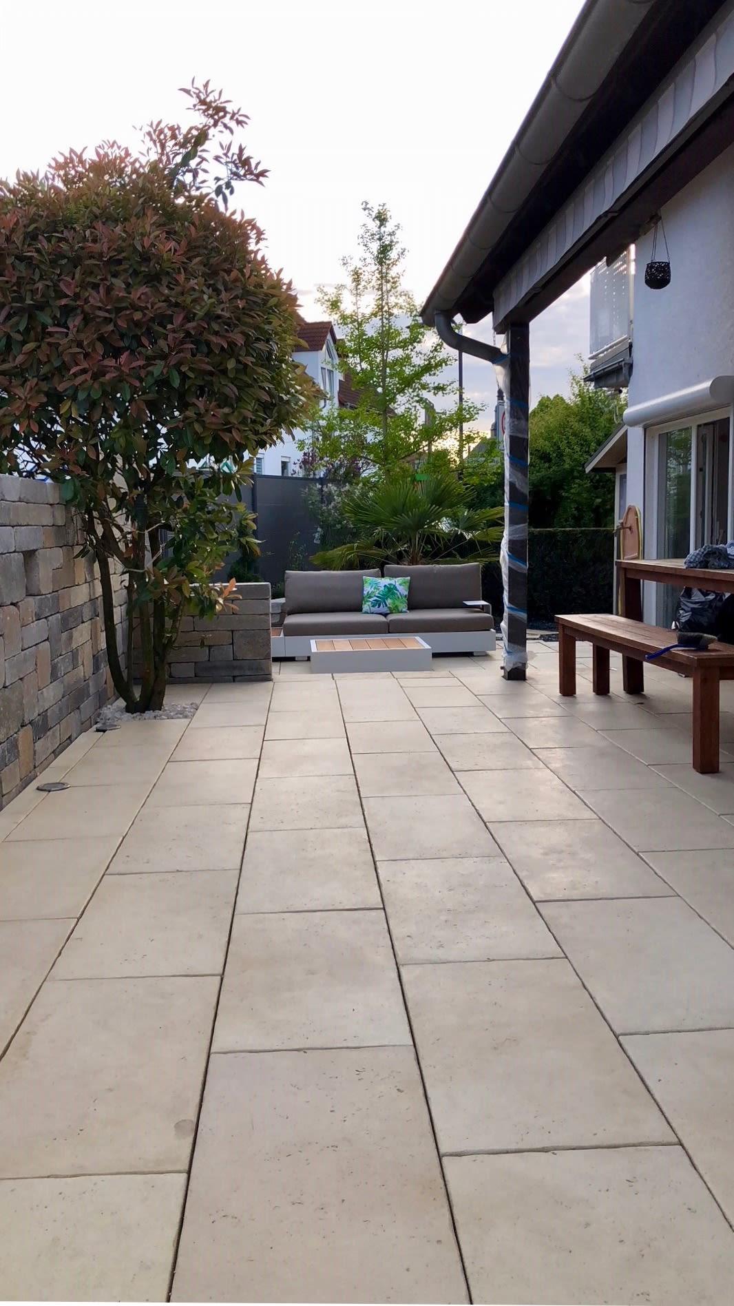 Terrasse mit Steinplatten und Holzsitzecke