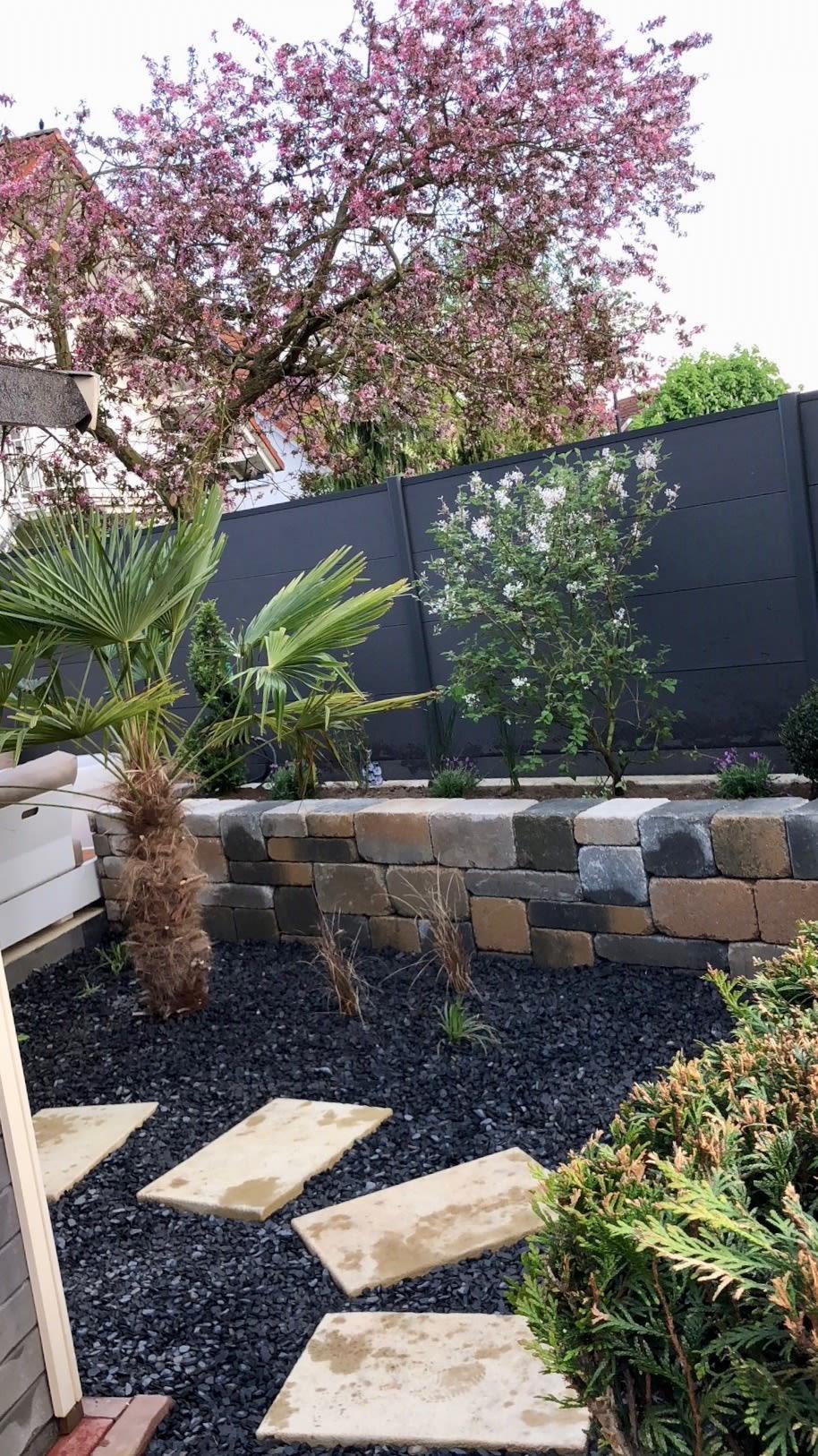 Gartengestaltung mit schwarzem Kies und Bepflanzung