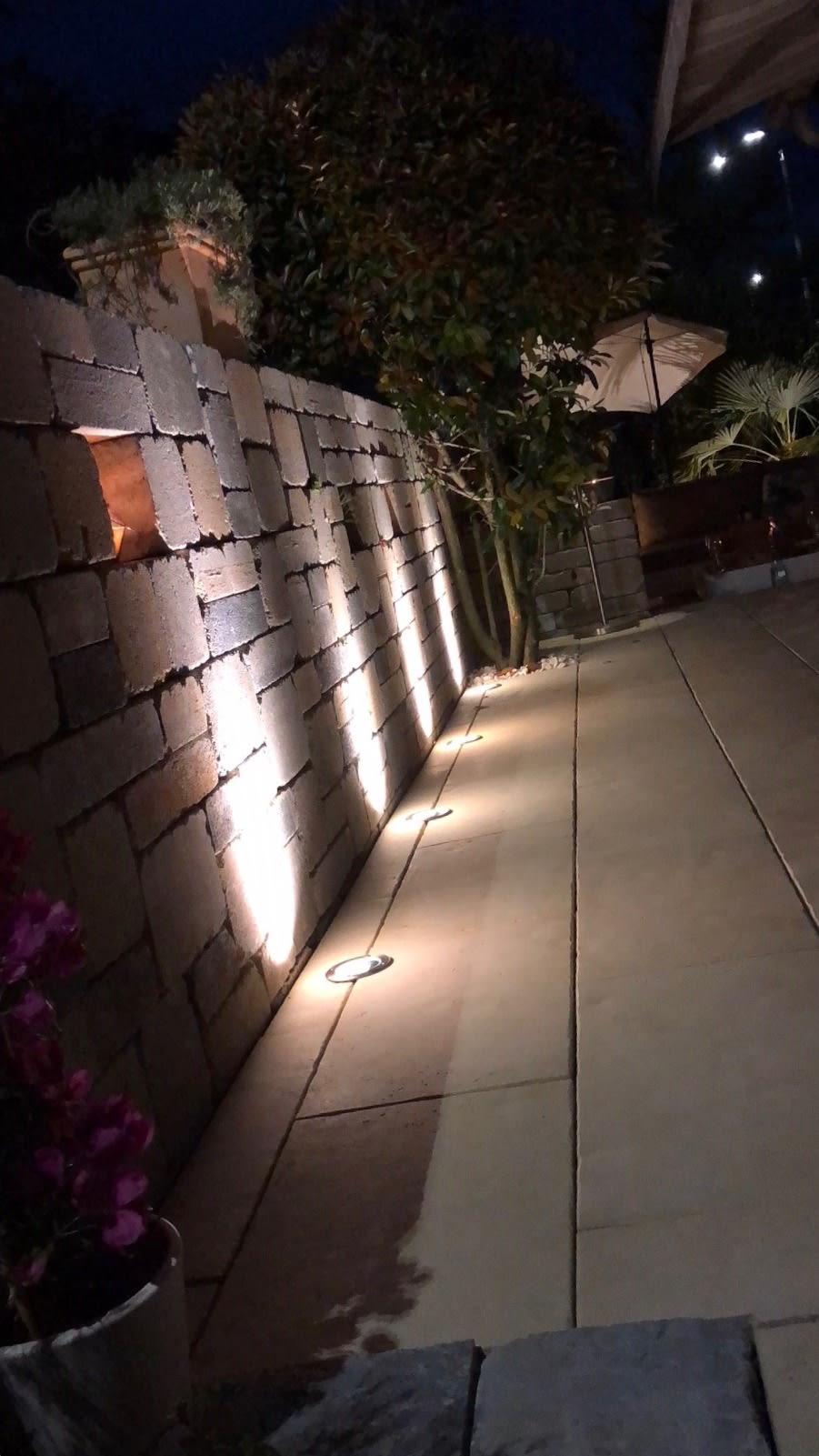 Terrasse mit Steinplatten Natursteinwand und Beleuchtung