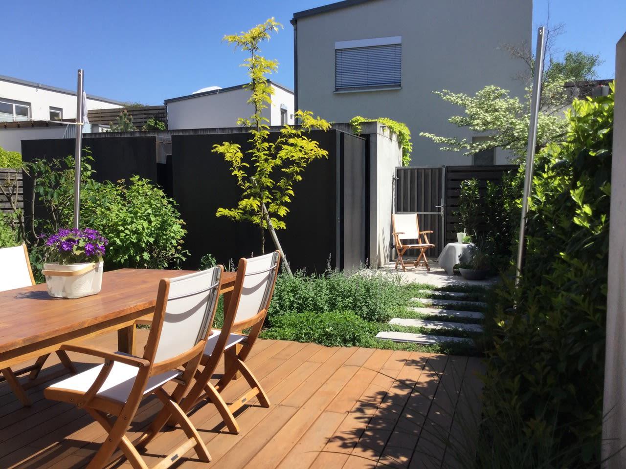 Garten mit Holzterrasse und Stühlen und Tischen Sicht auf Haus